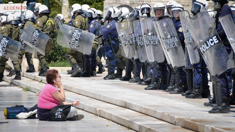 A protestor sits in front of the Greek police during an anti-austerity protest in Athens. May 11, 2011. (Watsons Wanderings/Creative Commons)