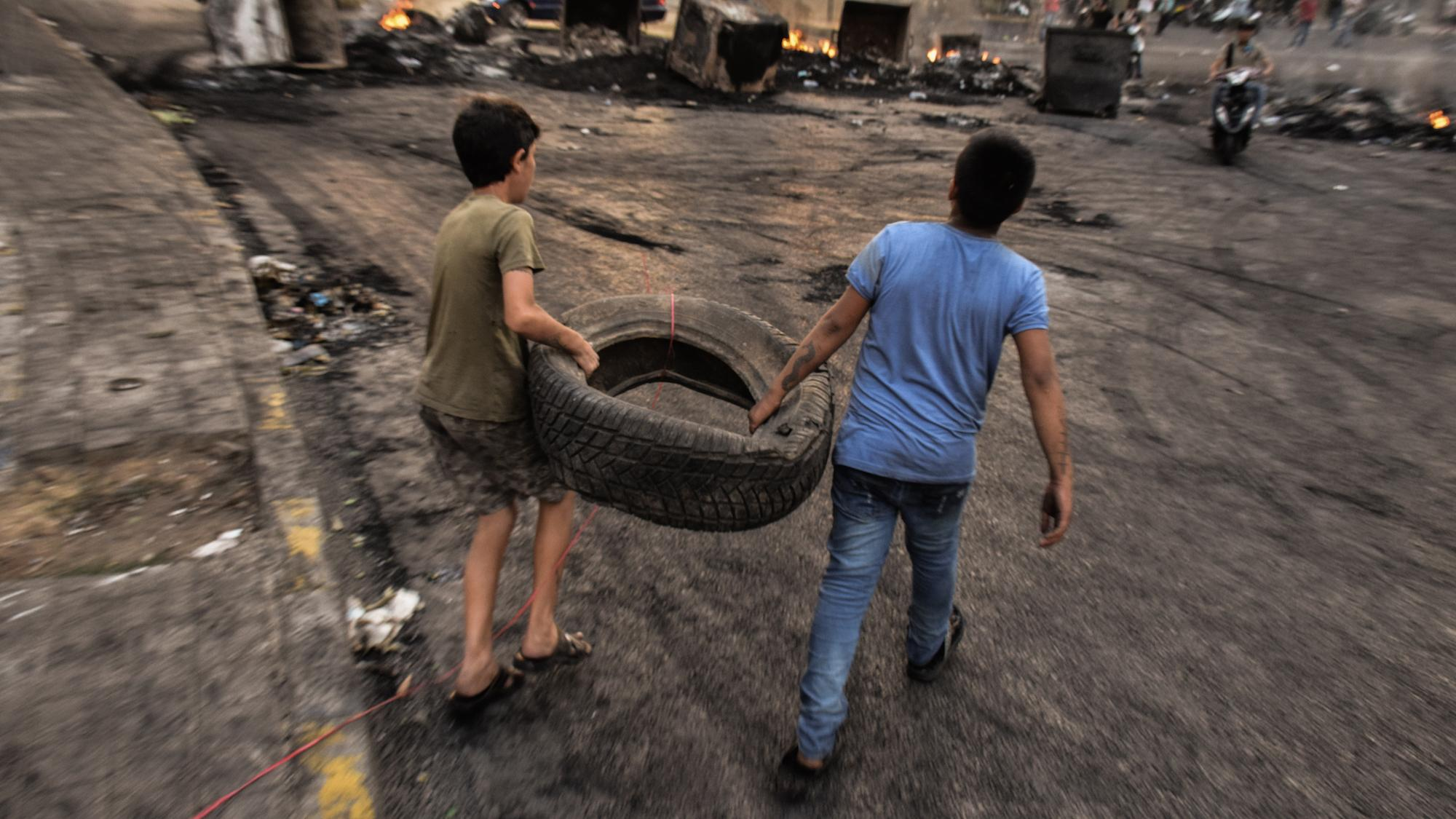 Two young boys carry a tire at a roadblock reinforced by burning dumpsters. Beirut, Lebanon. October 18, 2019. (Mouran Mattar/Fawra)
