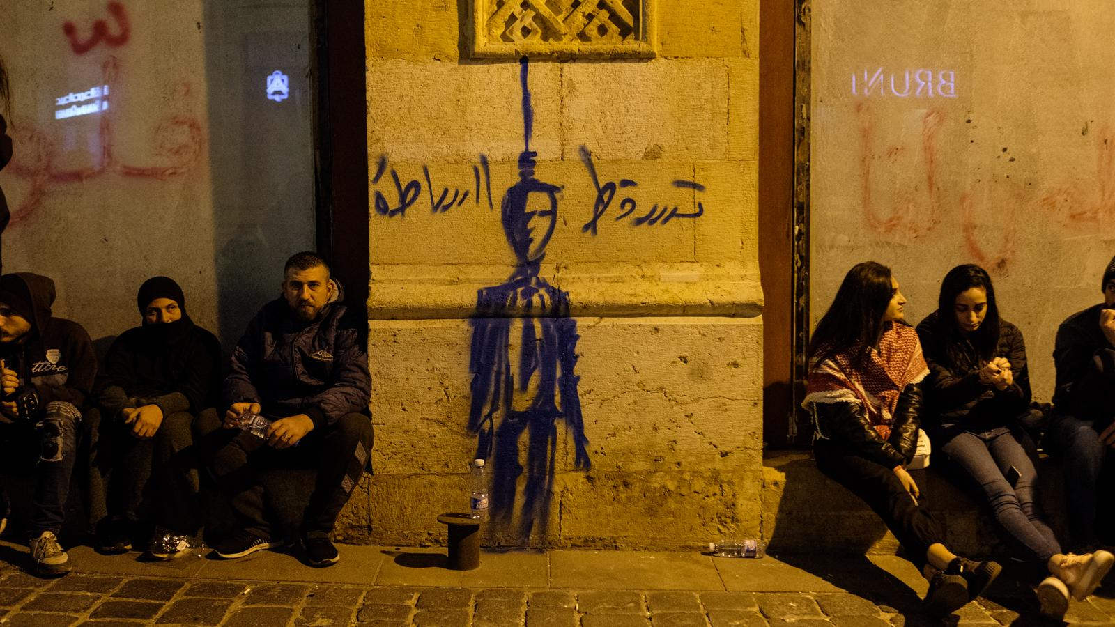 Protesters rest beside graffiti depicting the hanging of an authority figure. Downtown Beirut, Lebanon. December 15, 2019. (Rita Kabalan/The Public Source)