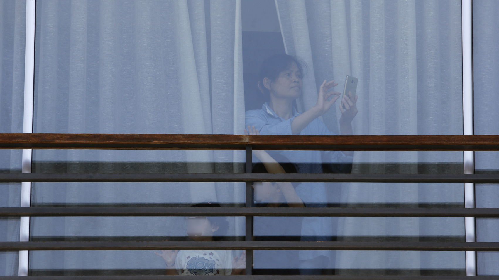 A migrant domestic worker films a May Day march as it passes by her employer's home. Beirut, Lebanon. May 1, 2020. (Marwan Tahtah/The Public Source)