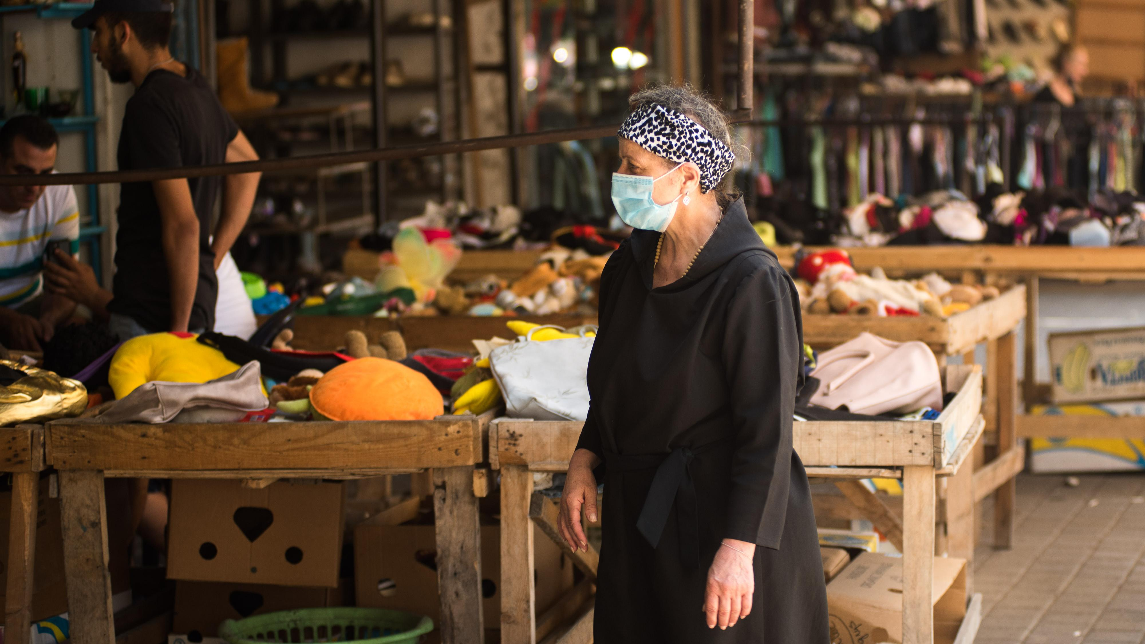 A woman donning a mask makes her way through a secondhand market in Tripoli near Nahr Abu Ali. Tripoli, Lebanon. June 13, 2020. (Natheer Halawani/The Public Source)