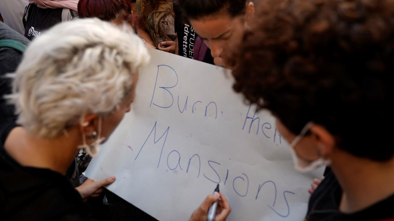 "Three protesters hold a sign in Riad al-Solh Square that reads, ""burn their mansions."" Beirut. Lebanon. October 18, 2019. (Mohamad Cheblak/The Public Source)"