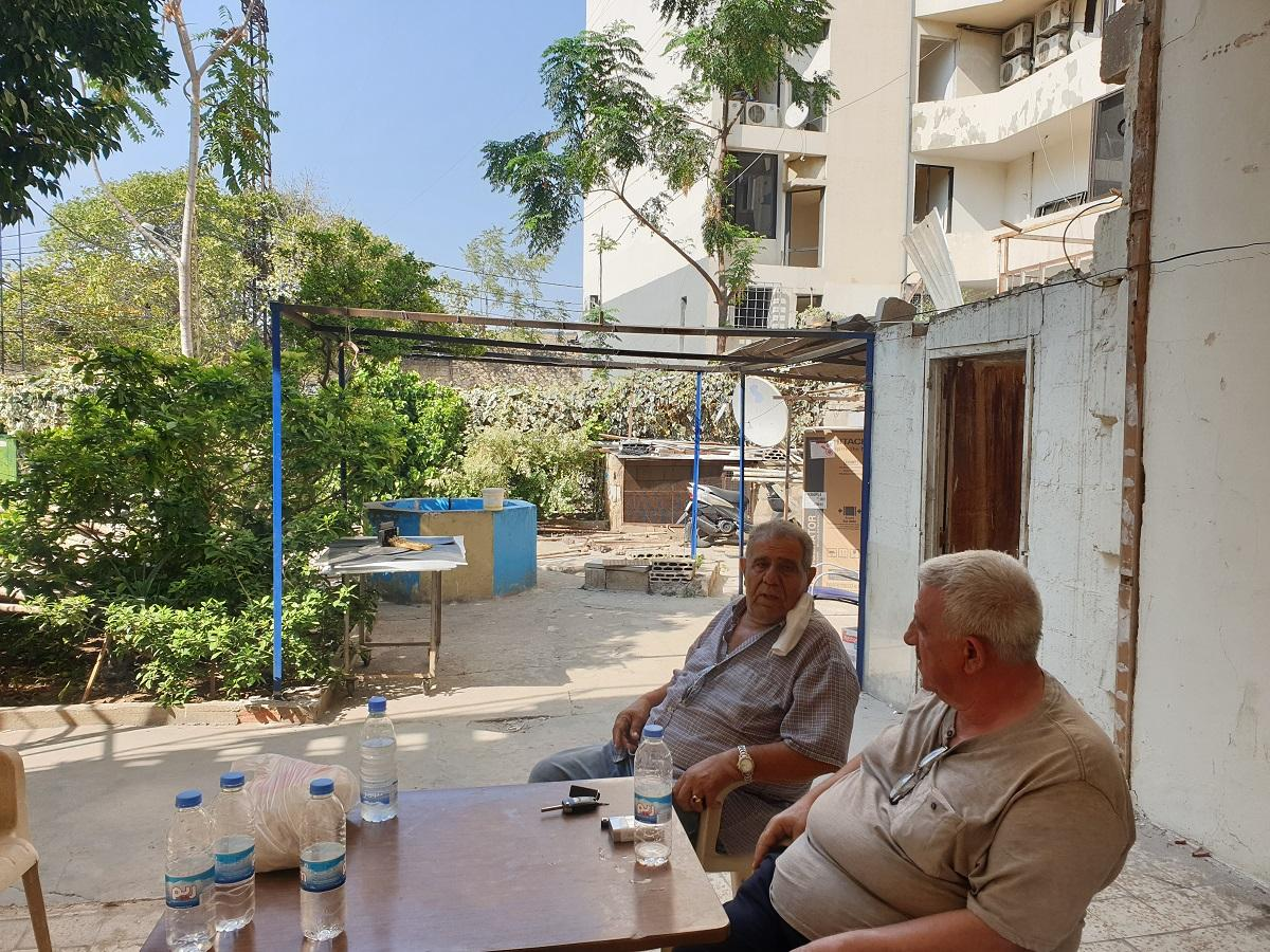 Two men engage in a conversation in front of their damaged house. Karantina, Beirut. August 31, 2020. (Batoul Yassine/The Public Source)