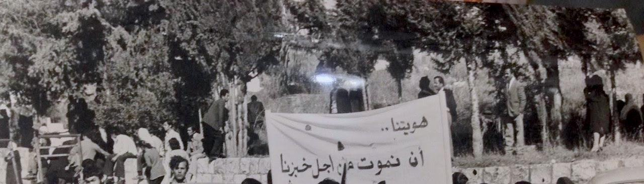 "Young women in factory uniforms hold a banner that reads, ""our identity is to die for our bread."" Date unknown. Source: Al-Anwar newspaper."