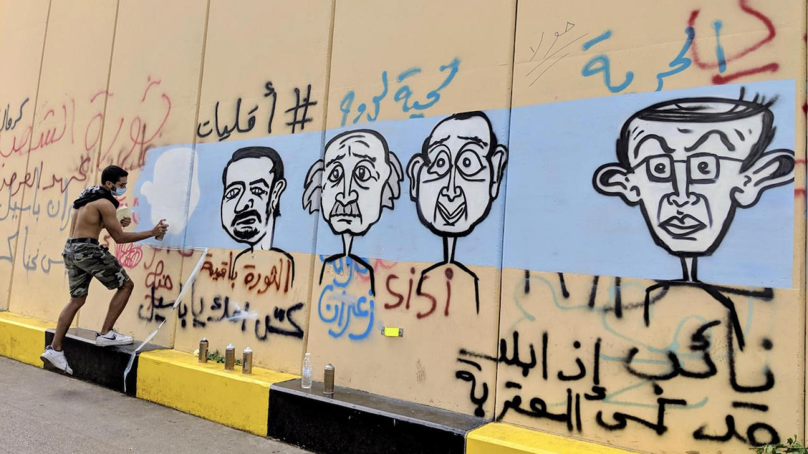 A graffiti artist paints a mural of some of Lebanon's oligarchs on a wall erected near Riad al-Solh Square in downtown Beirut. October 24, 2019. (Lara Bitar/The Public Source)