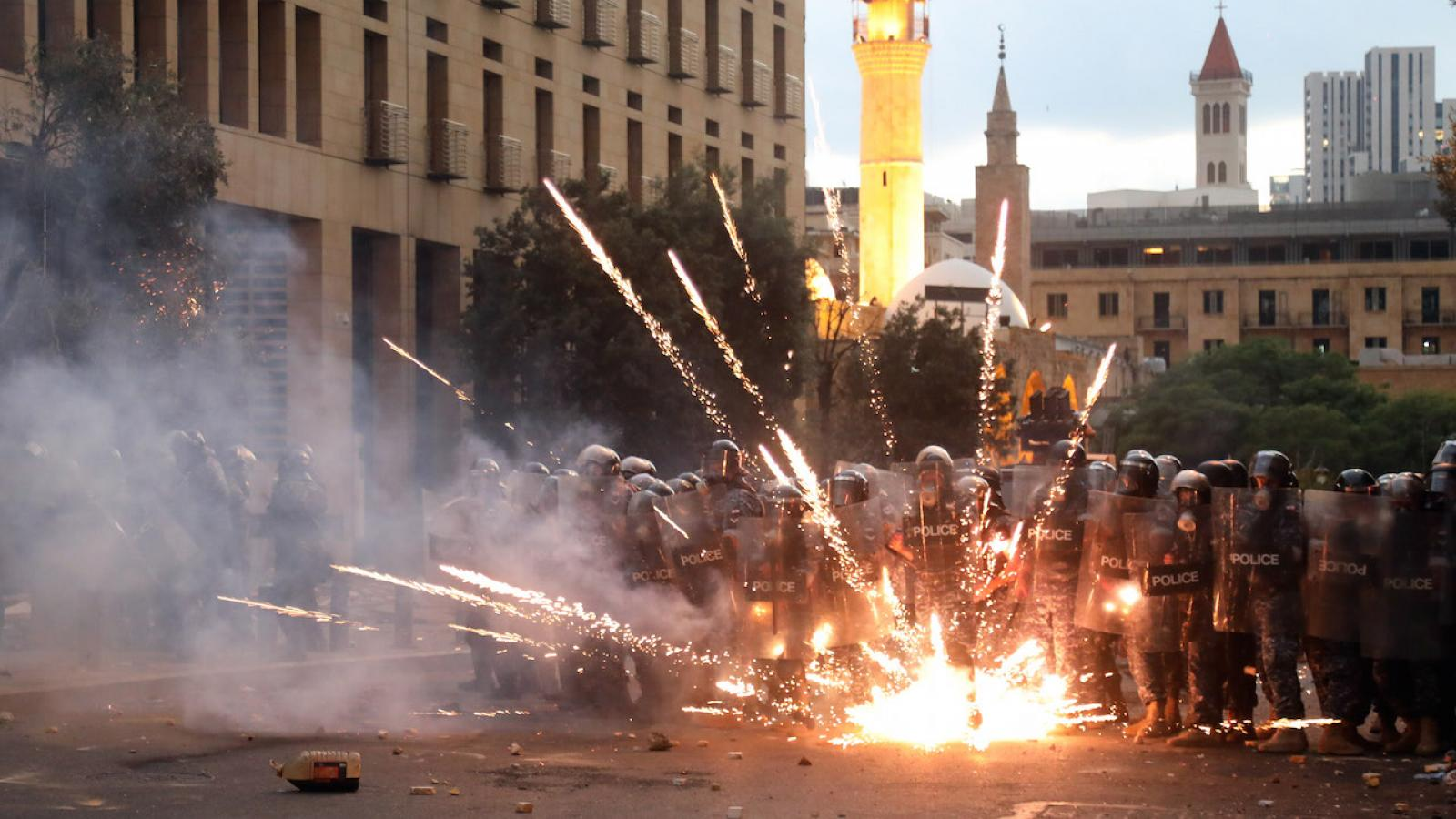 Protestors lob firecrackers at riot police in downtown Beirut.
